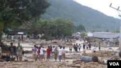 Penduduk menyaksikan kerusakan yang ditimbulkan oleh banjir bandang di Wasior, Papua Barat.