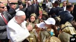 Le pape François salue les enfants habillés en costumes égyptiens anciens avant de célébrer la messe pour la petite communauté catholique égyptienne, au stade de défense aérienne au Caire, Egypte, 29 avril 2017.
