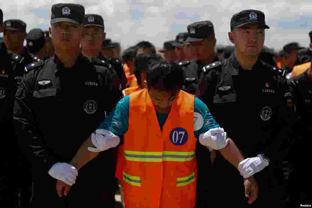 Chinese nationals (in orange vests), who were arrested in a suspected internet scam, are escorted by Chinese police officers before being deported, at Phnom Penh International Airport, in Phnom Penh, Cambodia.