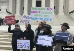 FILE - Activists rally outside the U.S. Supreme Court ahead of arguments in a key voting rights case involving a challenge to Ohio's policy of purging infrequent voters from voter registration rolls, in Washington, Jan. 10, 2018.
