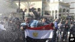 Des manifestants face aux canons à eau, au Caire