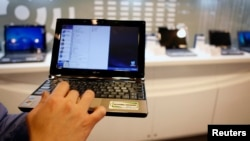 An employee poses with the low-cost Asus Eee PC laptop inside a mall in Taipei February 25, 2009. Netbooks have made headlines since their 2007 launch, making PCs accessible to millions of non-traditional users. But their cheap cost could also carry a ste