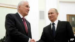 FILE - Russian President Vladimir Putin, right, and the leader of Georgia's breakaway province of South Ossetia Leonid Tibilov shake hands during their meeting in the Kremlin in Moscow, Russia, March 18, 2015.