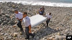 프랑스 경찰이 지난달 29일 인도양 섬에서 발견된 비행기 잔해를 운반하고 있다. 말레이시아 실종 여객기와 같은 기종인 보잉 777의 일부로 밝혀져 실종기 잔해 여부를 조사하고 있다.