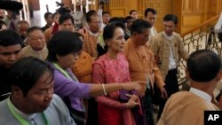 Aung San Suu Kyi, chairperson of National League for Democracy (NLD), center, arrives to participate in the inauguration session of lower house parliament in Naypyitaw, Myanmar, Feb. 1, 2016.