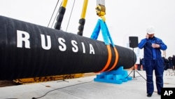 FILE - A Russian construction worker is seen next to a section of a natural gas pipeline.