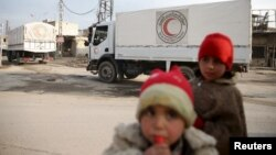 FILE - Children stand along a street as an aid convoy of the Syrian Arab Red Crescent and United Nations drives through the rebel-held besieged city of Douma, on the outskirts of Damascus, Syria, Feb. 23, 2016.
