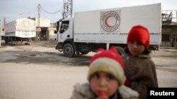 Сирійські діти біля машин з гуманітарною допомогою