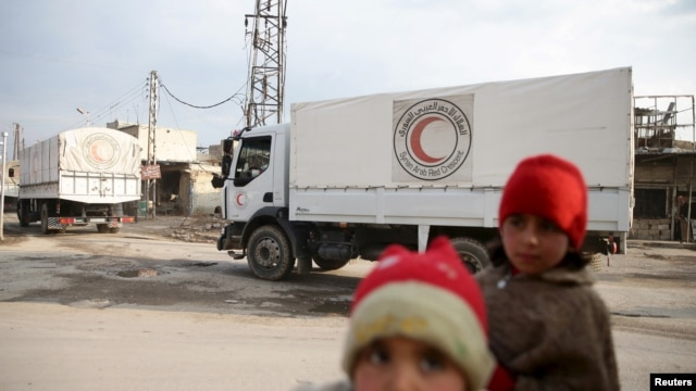Children stand along a street as an aid convoy of Syrian Arab Red Crescent and United Nation (UN) drives through the rebel held besieged city of Douma towards the besieged town of Kafr Batna to deliver aid, on the outskirts of Damascus, Syria, Feb. 23, 2016.