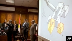 Egypt's Antiquities Minister Mamdouh el-Damaty, left, speaks during a press conference as he displays images of radar scans to King Tut's burial chamber on a projector, at the Antiquities Ministry in Cairo, Egypt, March 17, 2016. El-Damaty says analysis of scans of famed King Tut's burial chamber has revealed two hidden rooms that could contain metal or organic material.