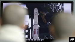 Para pendeta Budha menyaksikan peluncuran roket Korea Utara dari layar televisi di sebuah stasiun kereta api di Seoul, Korea Selatan (13/4).