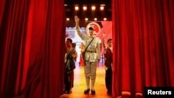 一名扮成共产党八路军的演员在山西武乡八路军文化园演出后向观众挥手。(2012年10月20日)