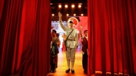 An actor dressed as an Eighth Route Army soldier waves after a performance at the Eighth Route Army Culture Park, one of two theme parks, in Wuxiang county, north China's Shanxi province, October 20, 2012.
