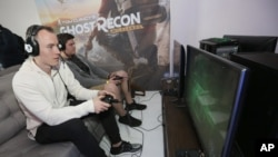 "Two players enjoy some quality time with a video game - ""Tom Clancy's Ghost Recon Wildlands: War Within the Cartel"" - during a livestream event, Feb. 16, 2017, in Los Angeles."