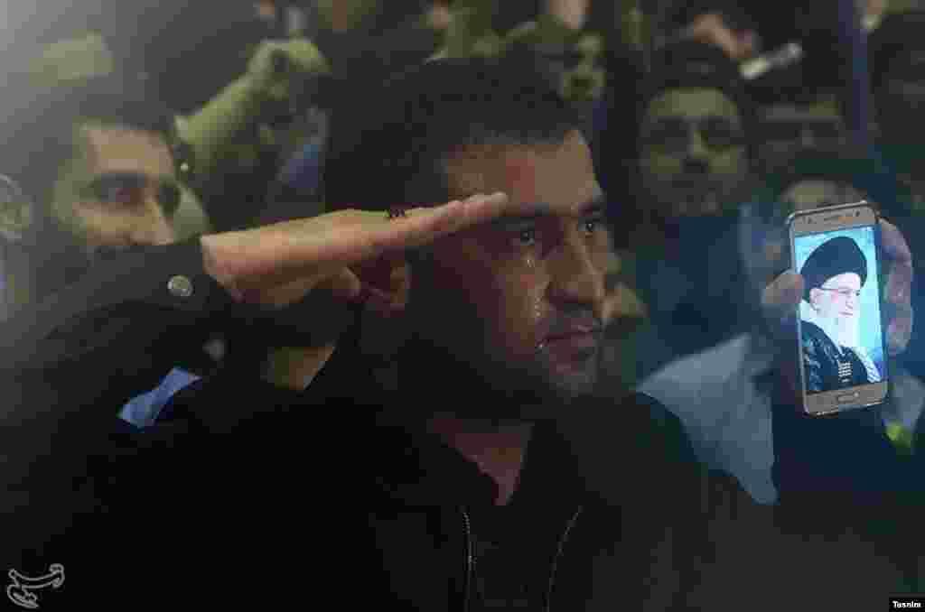 یک حامی ابراهیم رئیسی در همایش انتخاباتی او، عکسی از رهبر جمهوری اسلامی ایران در دست دارد و سلام نظامی می دهد. عکس: محمود حسینی