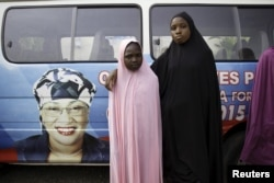 FILE – Girls pose near a vehicle bearing an image of Aisha Jummai Alhassan, the northeastern Taraba state candidate who would be Nigeria's first female governor, in Jalingo city, April 10, 2015.