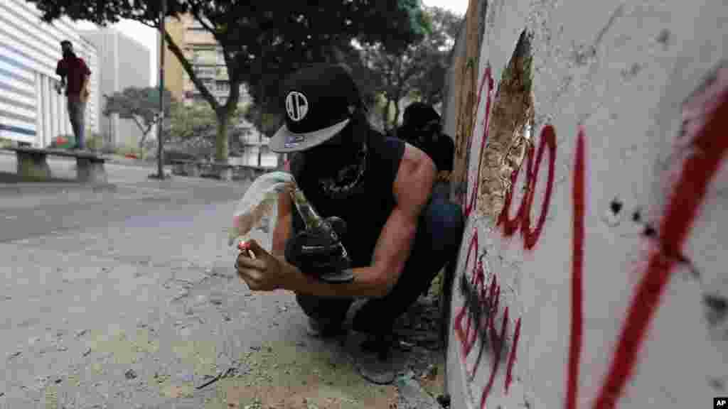 Un manifestante alista una bomba molotov para atacar a la policía, que intentaba disolver una manifestación en Caracas.