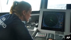 Carmen McGregor checks the radar system on July 18, 2021, as part of the ship's 18-day voyage to observe up close the activities of the Chinese distant water fishing fleet off the west coast of South America.