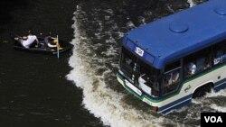 Warga mendayung perahu saat sebuah bus melintas jalanan yang tergenang air di Bangkok, Thailand (5/11).