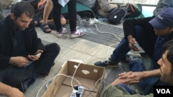 Outside Vienna train station, aid workers provide what many refugees want most: electricity to charge mobile phones that kept them alive and on track so far, Sept. 15, 2015. (H. Murdock / VOA)