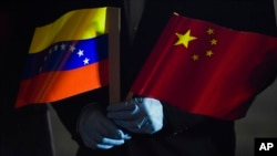 FILE - In this March 30, 2020, photo, Venezuela's Foreign Minister Jorge Arreaza holds Venezuelan and Chinese flags as medical specialists and supplies arrive from China at the Simon Bolivar International Airport in La Guaira, Venezuela.