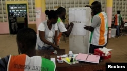 Polling agents count ballots at a polling station during the referendum for a new constitution, in Abidjan, Ivory Coast, Oct. 30, 2016.