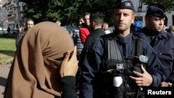 Seorang perempuan yang mengenakan niqab atau cadar menutup wajahnya saat pemeriksaan kartu identitas di kota Lille, Perancis (foto: dok).