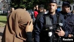 Seorang perempuan yang mengenakan jilbab dan cadar menutup matanya saat berada di dekat polisi Perancis (foto: dok).