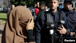 A woman wearing a full-face veil, or niqab, covers her eyes as she stands near police in Lille, France, in this September 22, 2012, file photo.