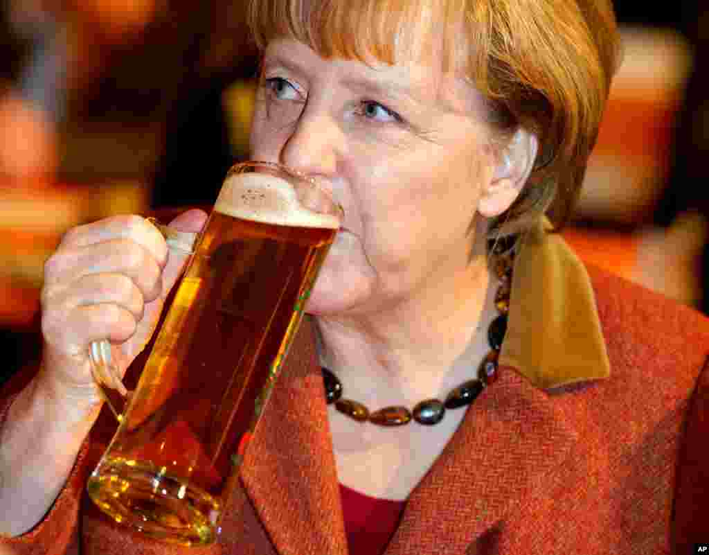 German chancellor Angela Merkel drinks beer during a political Ash Wednesday meeting of her Christian Democratic Party, CDU, in Mecklenburg-Western Pomerania , in Demmin, eastern Germany.