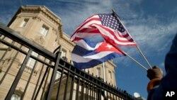 一名古巴裔美国人在古巴驻华盛顿新开使馆前挥舞两国国旗庆祝 (2015年7月21日)。