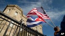 Edwardo Clark, một người Mỹ gốc Cuba, cầm quốc kỳ Mỹ và quốc kỳ Cuba đứng bên ngoài đại sứ quán mới mở của Cuba tại Washington, 20/7/2015.