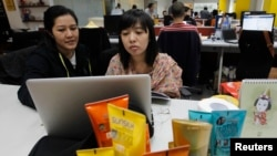 Social media strategists work to prepare a campaign through Twitter at an advertising agency in Jakarta, March 26, 2013.