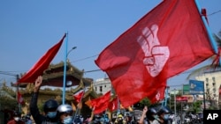Engineers carry flags bearing the three-fingers salute as they drive their motorcycles during an anti-coup protest in Mandalay, Myanmar on Thursday March 25, 2021.