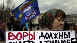 "A member of the opposition holds a banner at a protest near the Kremlin, April 16, 2011. The banner reads, ""Thieves should go to jail"" and displays images of Prime Minister Vladimir Putin."