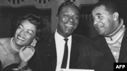 """Nat """"King"""" Cole (center) with baseball player Roy Campanella and his wife Ruthe at New York City's Copacabana night club"""