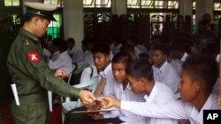 Tentara Burma (kiri) memberikan kartu identitas untuk anak-anak dibawah umur 18 tahun yang direkrut menjadi tentara dalam sebuah upacara serah terima di Rangoon (Yangon) (Foto:: dok).