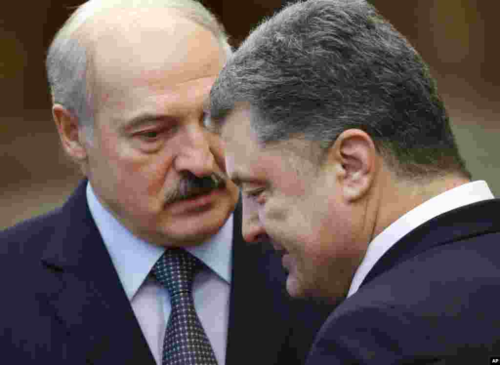 Ukrainian President Petro Poroshenko, right, speaks with Belarus President Alexander Lukashenko after the peace talks in Minsk, Belarus, Feb. 12, 2015.
