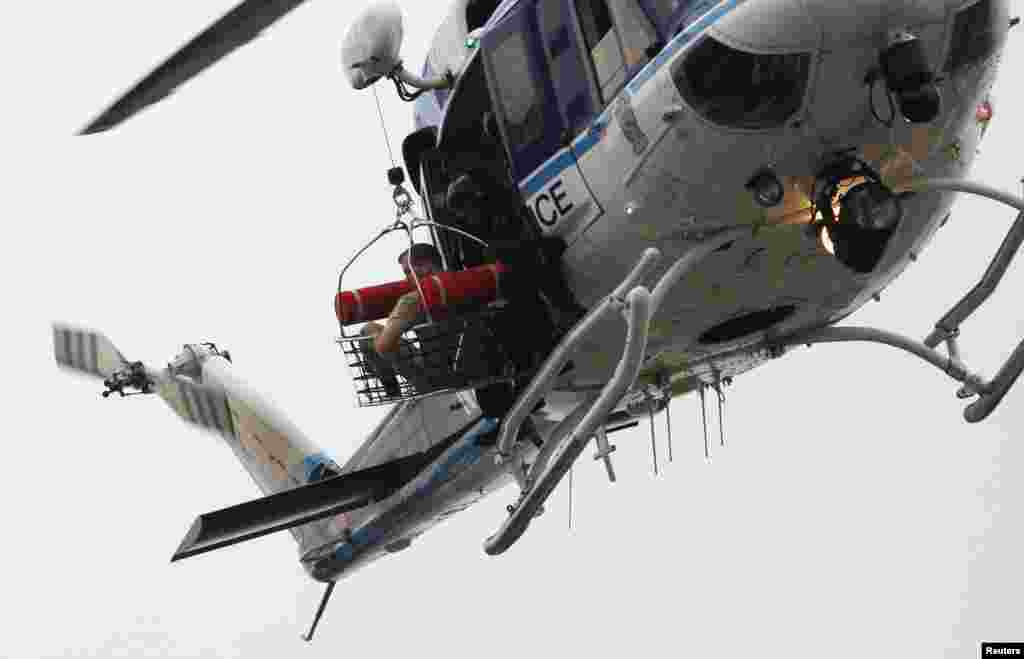 A police helicopter lifts what appears to be a shooting victim up as it hovers over a rooftop on the Washington Navy Yard, Sept. 16, 2013.