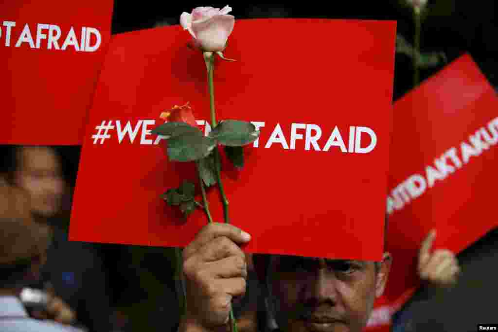 "People hold placards reading ""We are not afraid"" during a rally at the scene of Thursday's deadly gun and bomb attack in central Jakarta, Indonesia."