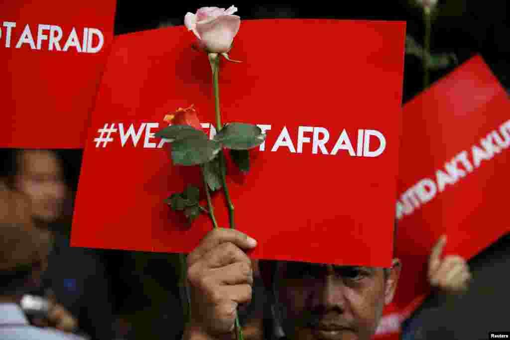 """Người biểu tình cầm biểu ngữ viết """"Chúng tôi không sợ"""" trong một cuộc tập hợp tại hiện trường vụ tấn công bằng súng và bom làm chết người hôm thứ Năm ở trung tâm thủ đô Jakarta, Indonesia."""