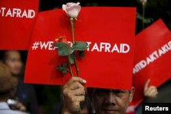 "People hold placards reading ""We are not afraid"" during a rally at the scene of Thursday's gun and bomb attack in central Jakarta, Indonesia, Jan. 15, 2016."