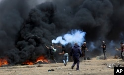FILE - A Palestinian protester throws back a tear gas canister at Israeli soldiers as others burn tires near the Israeli fence during a protest at the Gaza Strip's border with Israel, May 11, 2018.