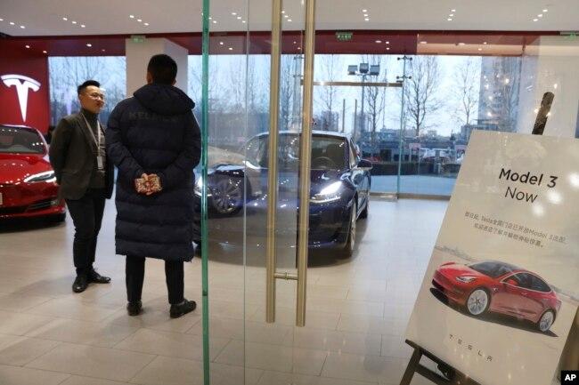 Un vendedor habla con un cliente en una tienda de Tesla en Beijing, China, el lunes, 7 de enero de 2019.