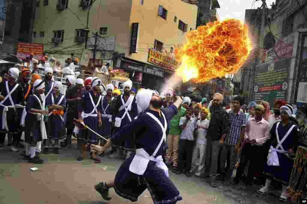 Một người Sikh biểu diễn tiết mục phun lửa trong một đám rước vào hôm trước ngày lễ kỷ niệm ngày sinh của Bậc thầy Ram Das ở Amritsar, Ấn Độ. Ram Das là người thứ tư trong mười bậc thầy guru của đạo Sikh.