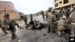 美军与阿富汗士兵8月14日在帕尔旺省省长官邸外检查自杀炸弹爆炸现场