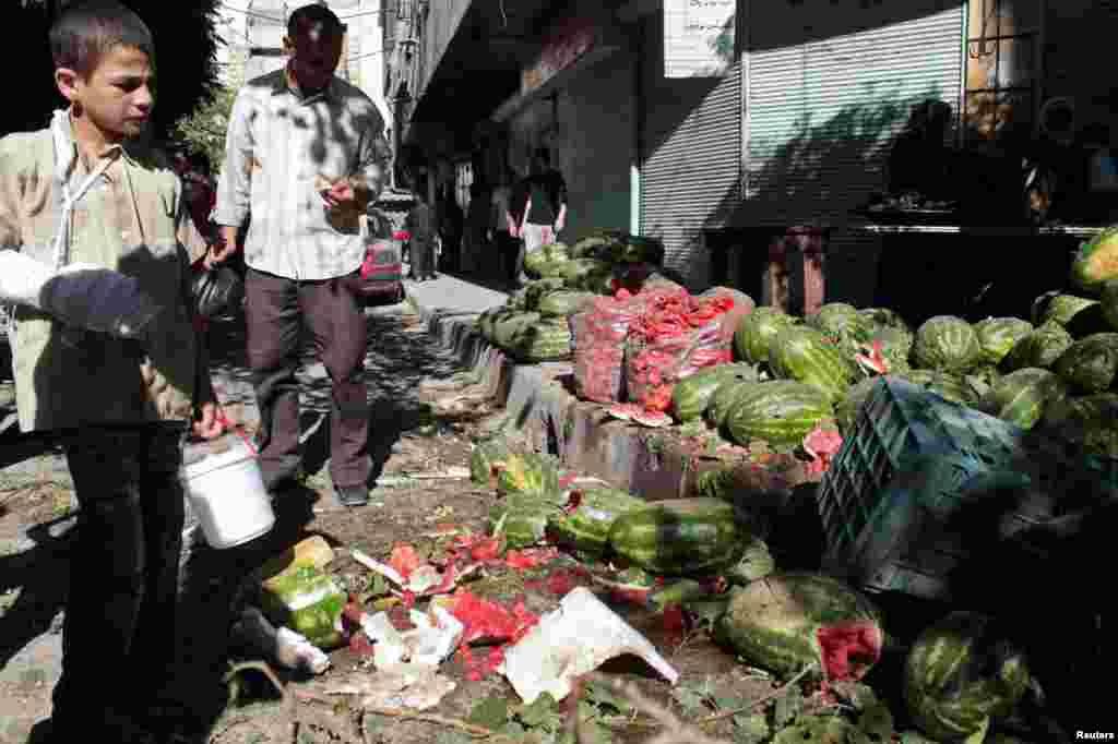 An injured youth at a vegetable market hit by what activists said was shelling by forces loyal to Syria's President Bashar al-Assad at al-Mashhad district in Aleppo, July 31, 2013.