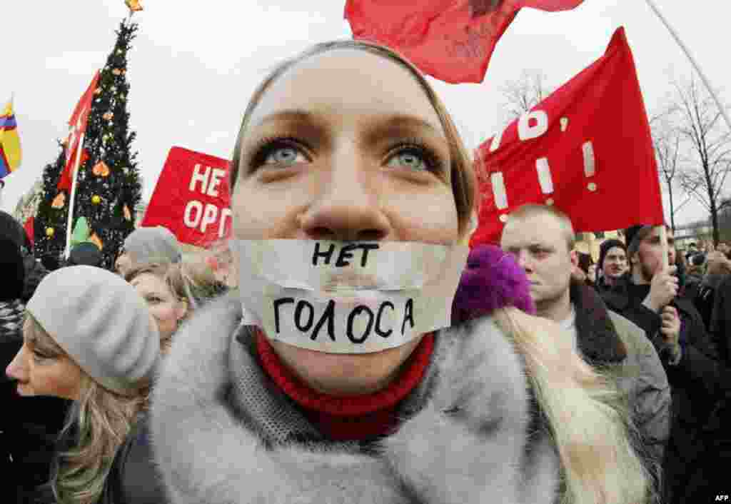 "A protester stands during a rally in downtown St. Petersburg, Russia, Saturday, Dec. 10, 2011. The sign reads ""No vote."" More than 10,000 people have protested in St. Petersburg against Prime Minister Vladimir Putin and his party, which won the largest sh"
