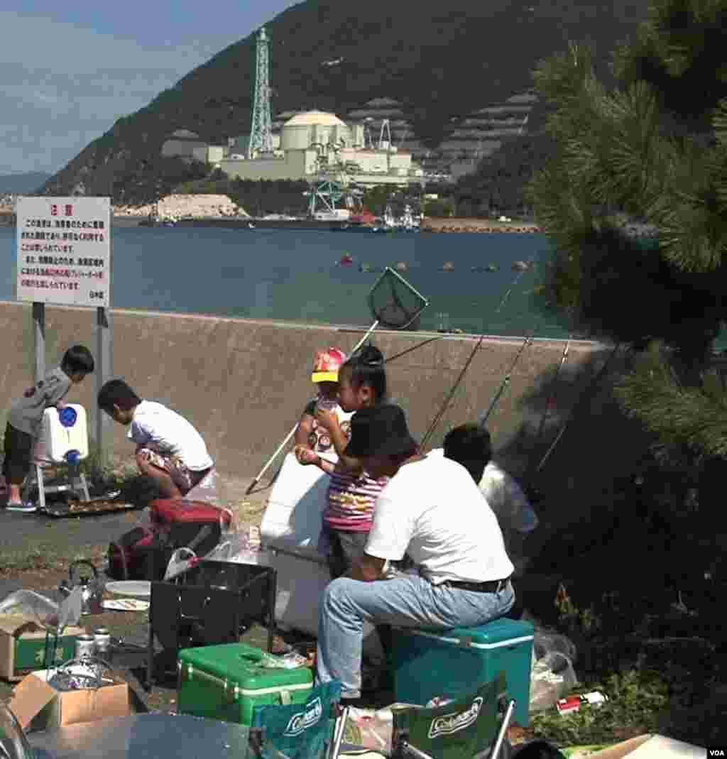A family picnics across the bay from the Monju nuclear reactor facility in Fukui Prefecture, Japan, Sep. 25, 2012. (S. Herman/VOA)