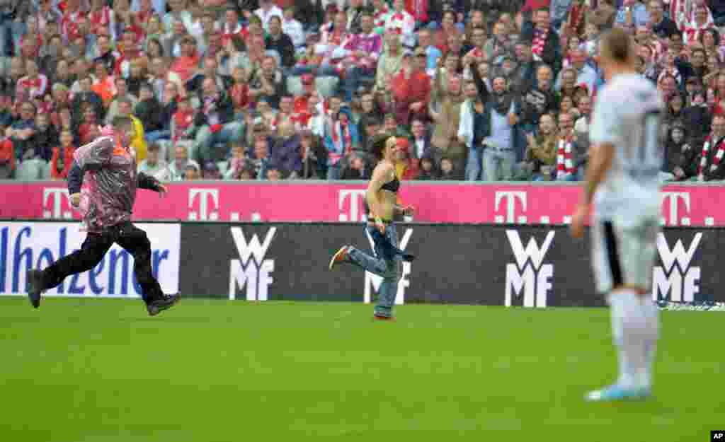 Một nhân viên an ninh rượt theo một phụ nữ không mặc áo ngoài trên sân cỏ trong trận bóng đá giữa hai đội FC Bayern Munich và FC Freiburg tại Munich, Đức.